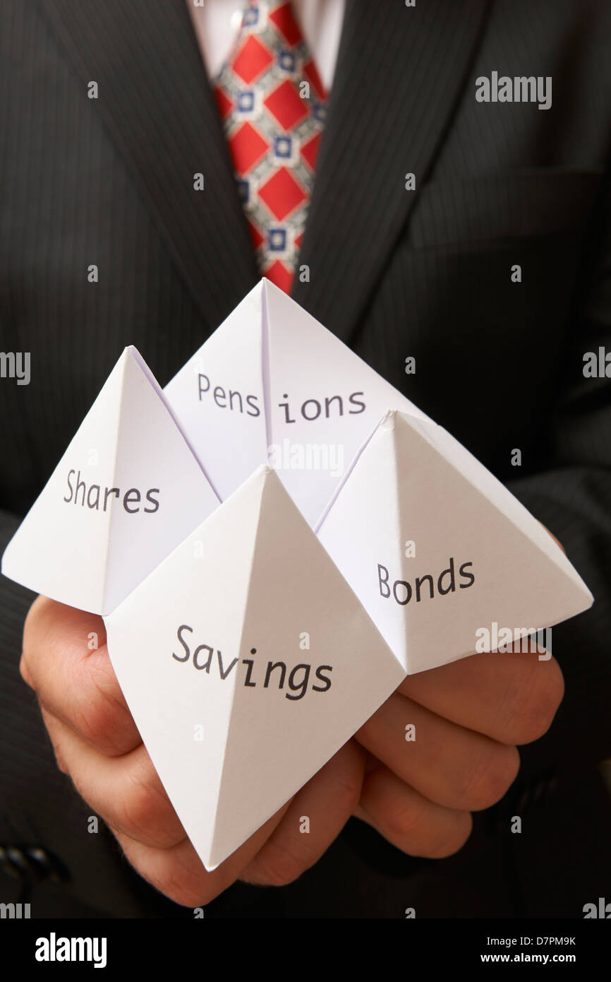 Business man holding paper origami fortune teller with savings,bonds,shares and pensions written on it - Stock Image