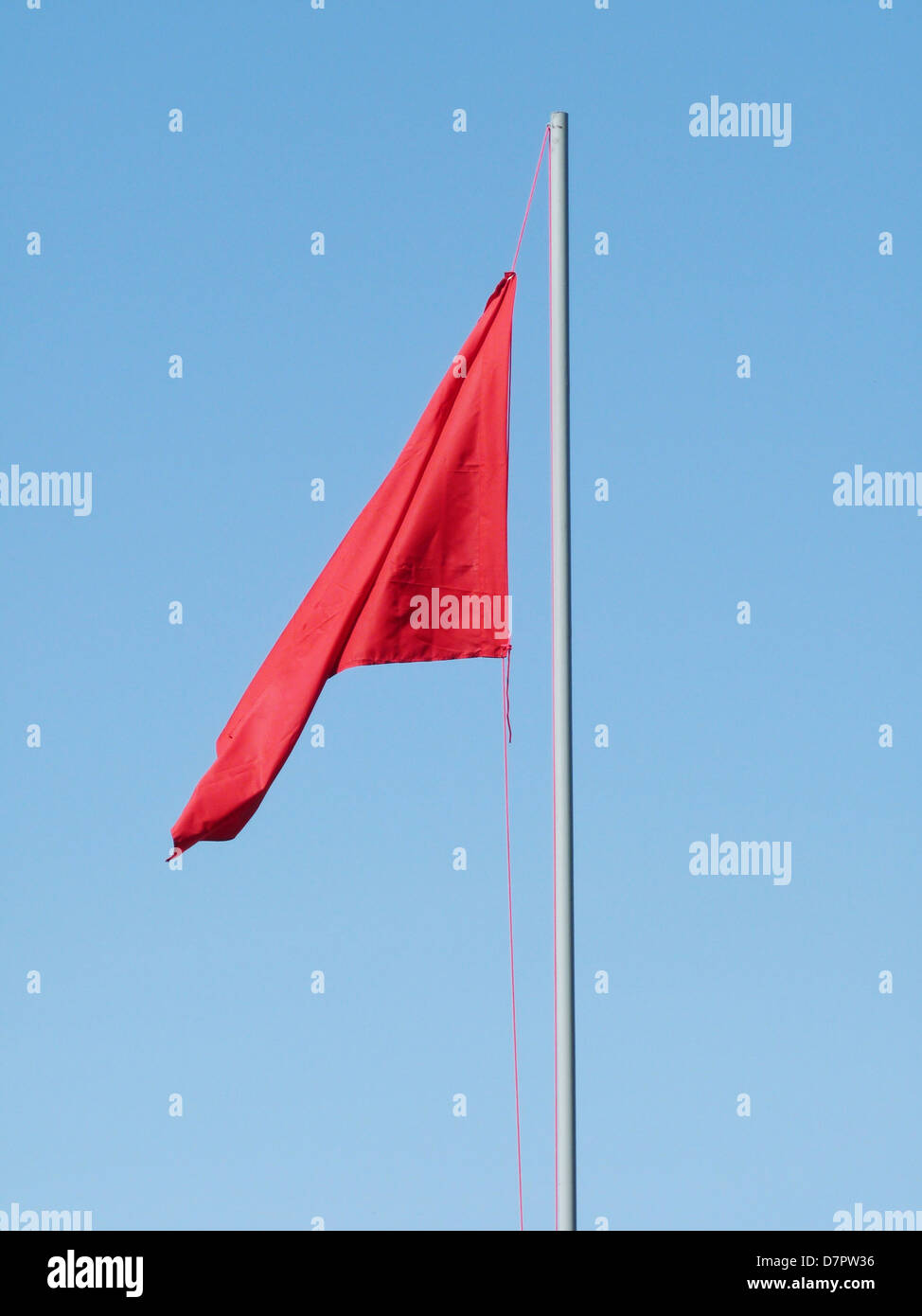 red flag communism totalitarian regime politics banner flag is raised unfreedom staff wind high day holiday blue Stock Photo