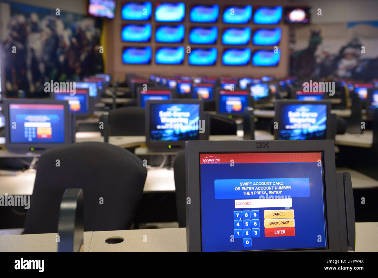Empty room of computer screens for self-serve wager betting on horse races at Woodbine Racetrack Toronto - Stock Image