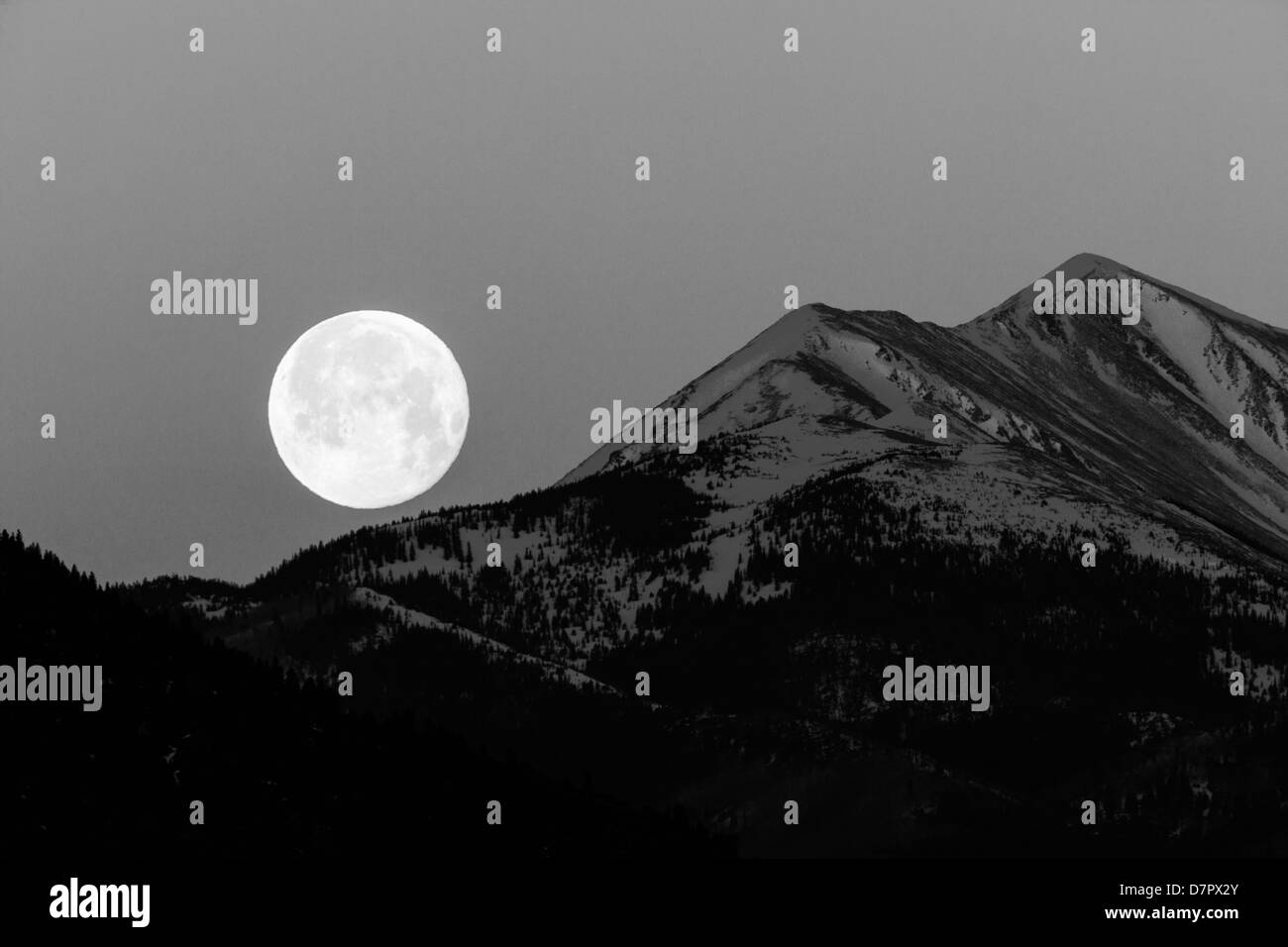 Black and white view of full moon setting over Rocky Mountains, Salida, Colorado, USA Stock Photo