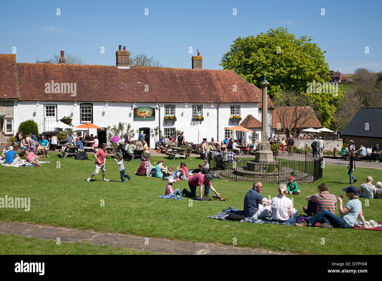 English village pub The Tiger at East Dean, East Sussex. Busy on a bank holiday Monday ppl sit on the green and - Stock Image