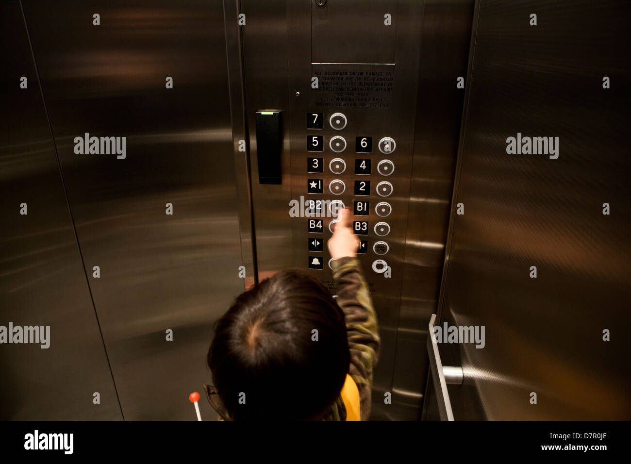 Child pushing elevator floor button - USA - Stock Image
