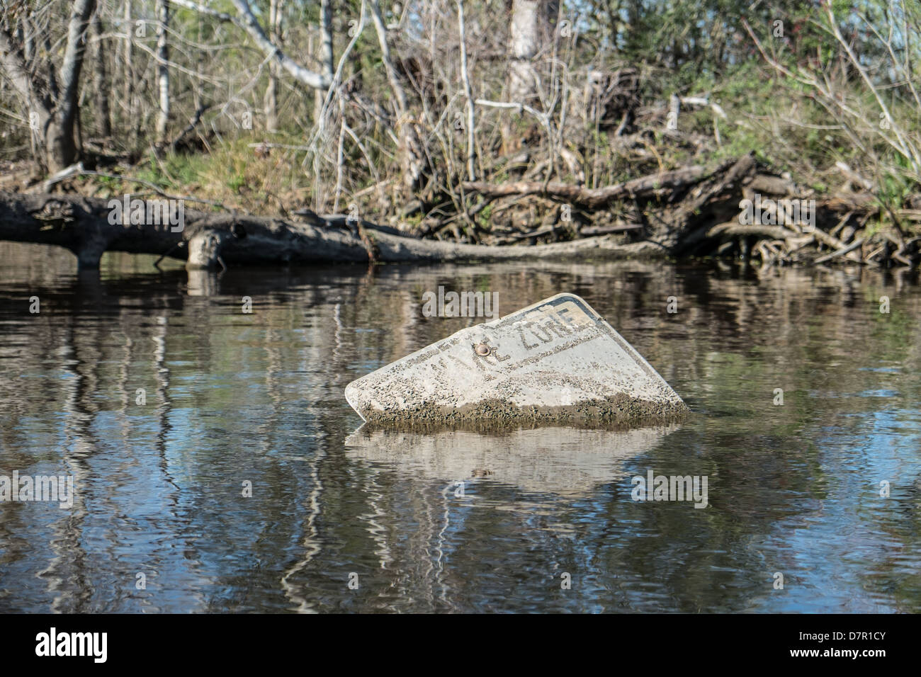 A 'No Wake' sign submerged in swamp water - Stock Image