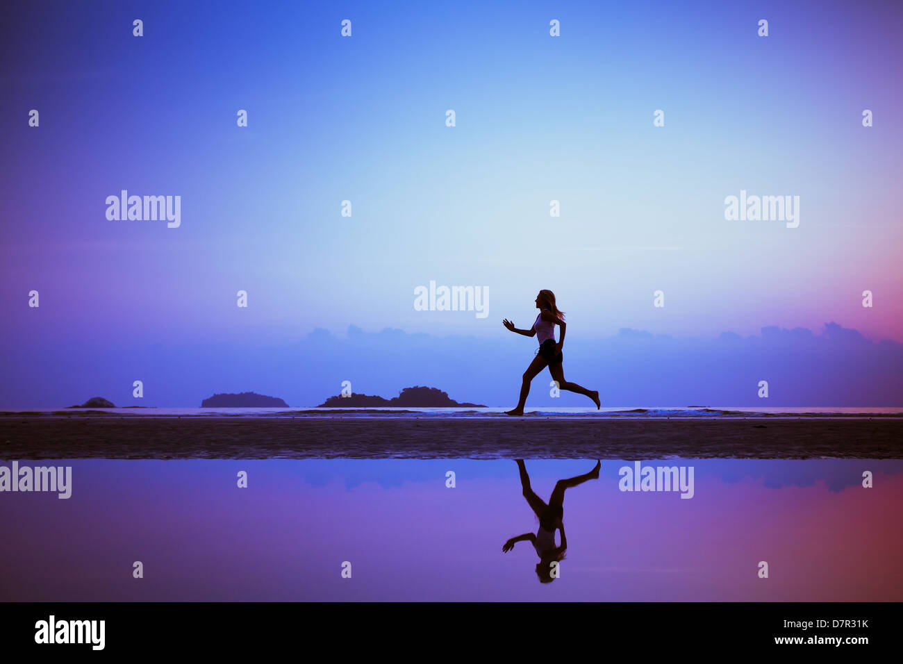 sport background, run to purpose, woman silhouette on the beach - Stock Image