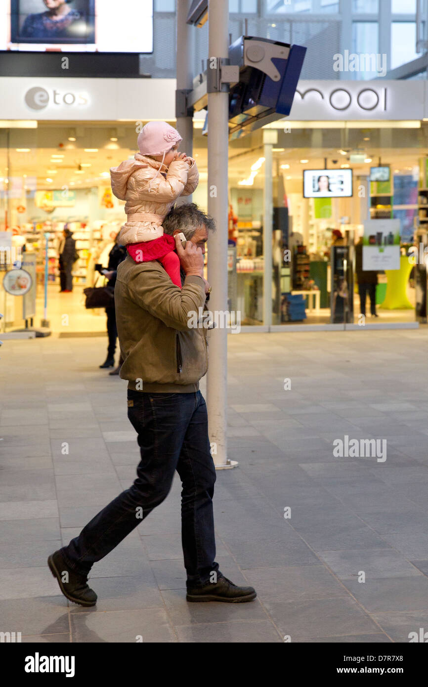 man on phone toddler on shoulders - Stock Image