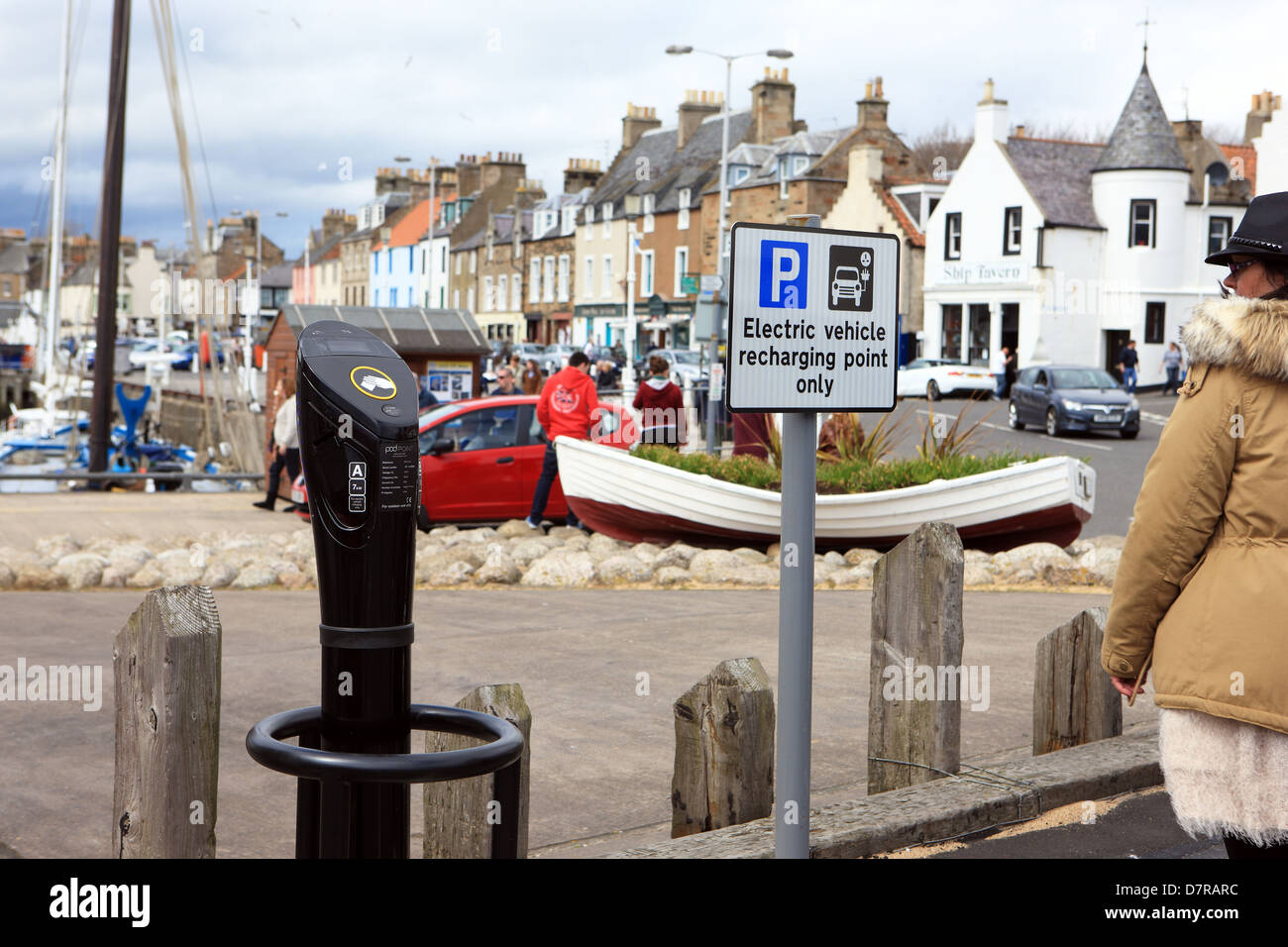 Woman looking at a Pod Point parking charger for an electric car in the Fife coastal town of Anstruther - Stock Image