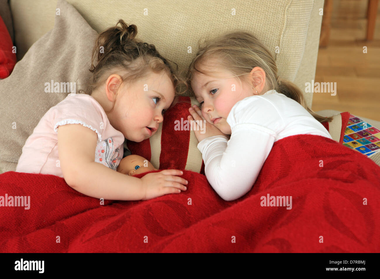 Younger sister showing concern towards her older sister who is not feeling well and is lying on the couch with a Stock Photo
