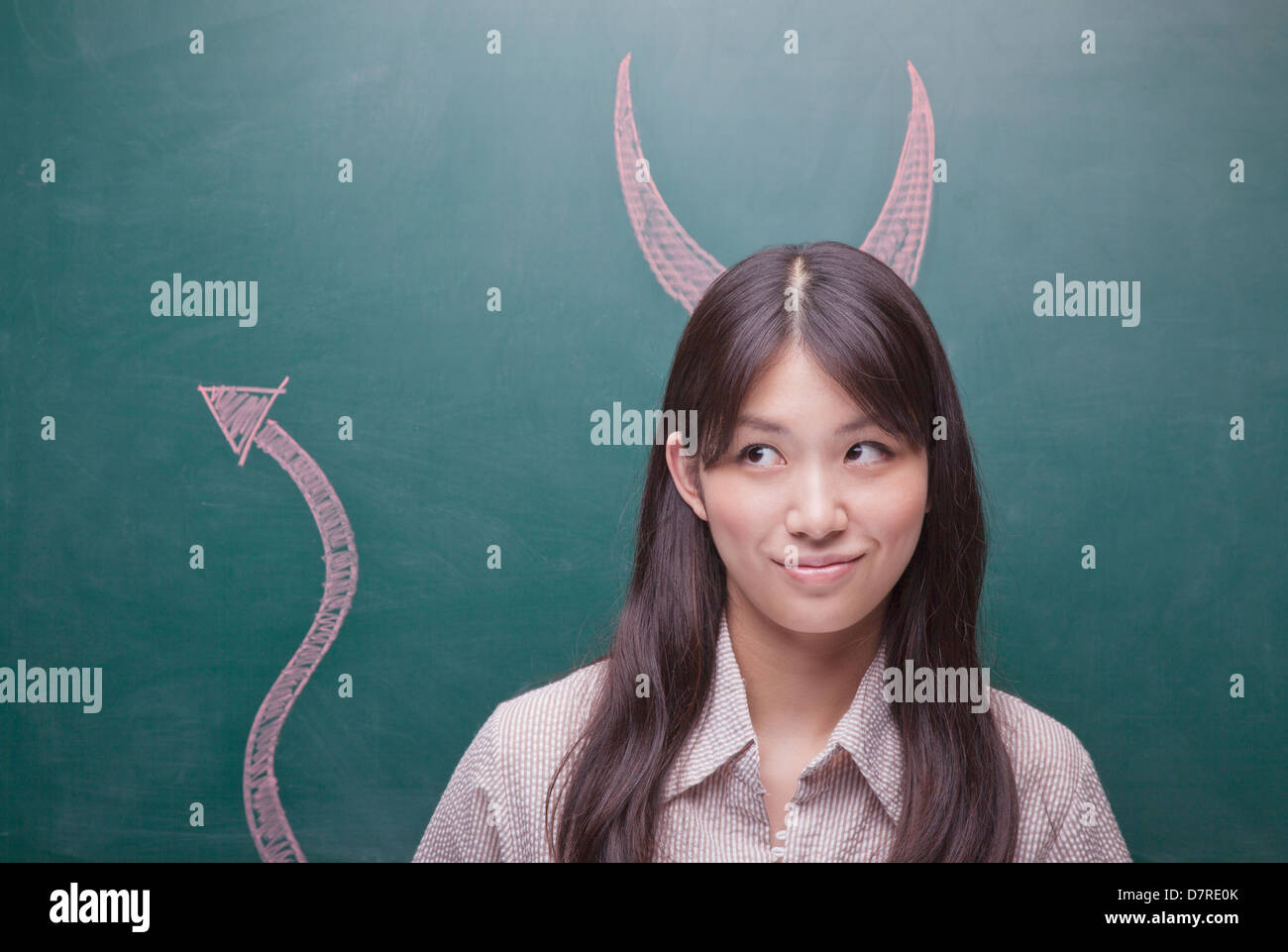 Young woman with devil horns and tail on blackboard Stock Photo