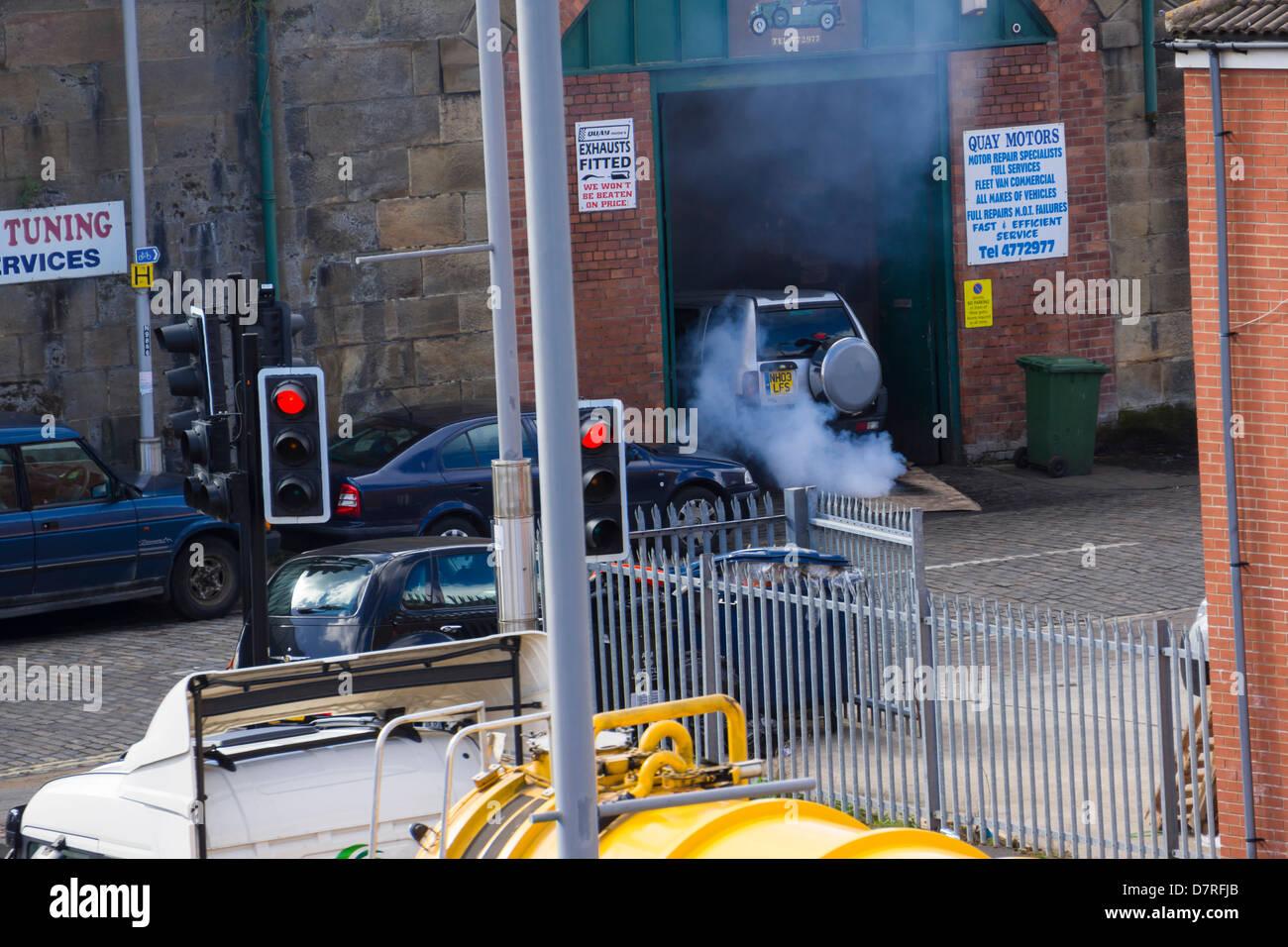 An old car emitting smoke at a garage. Stock Photo