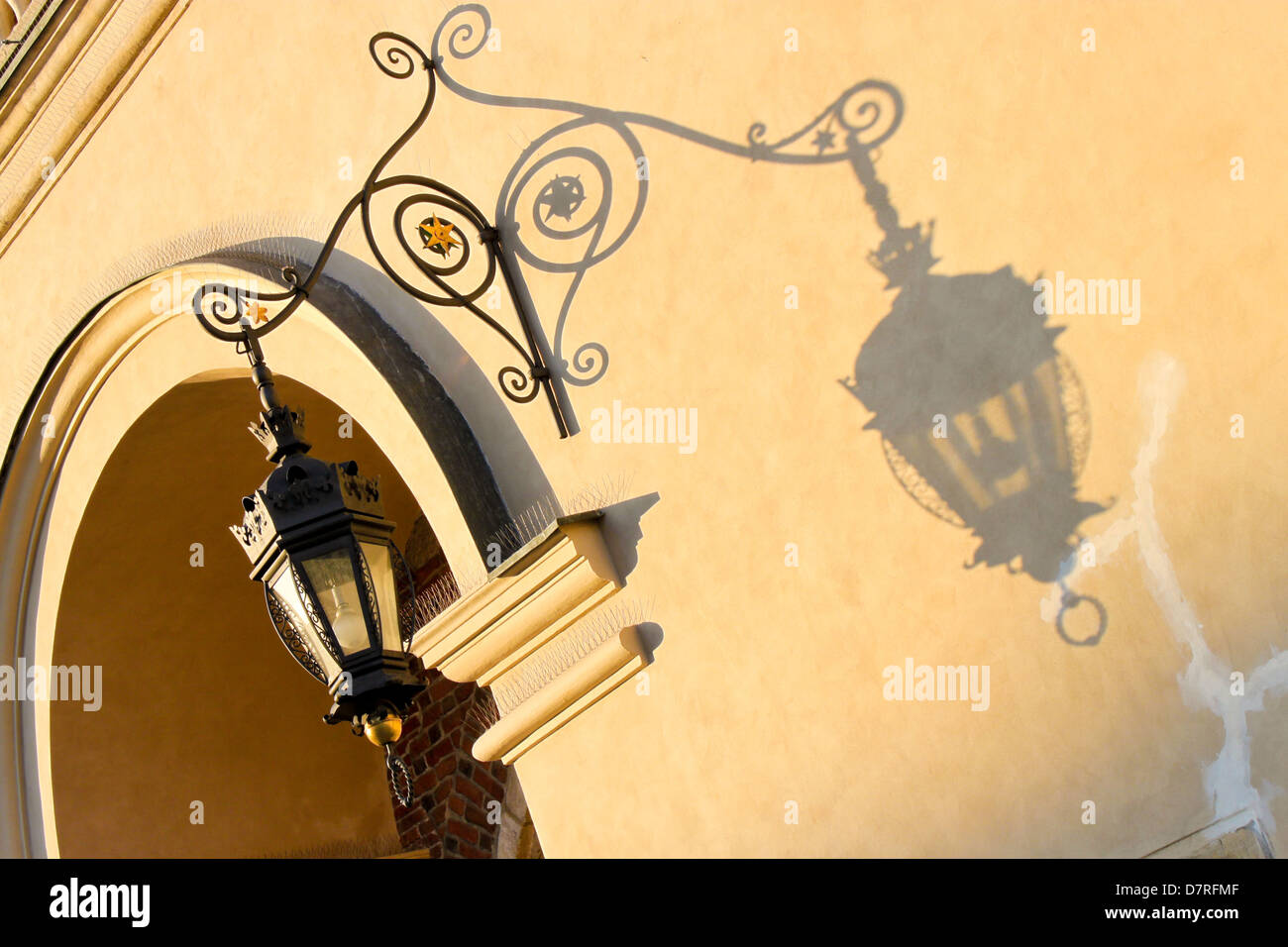 wrought-iron lantern casts a shadow on a wall of Cloth Hall in Stock ...