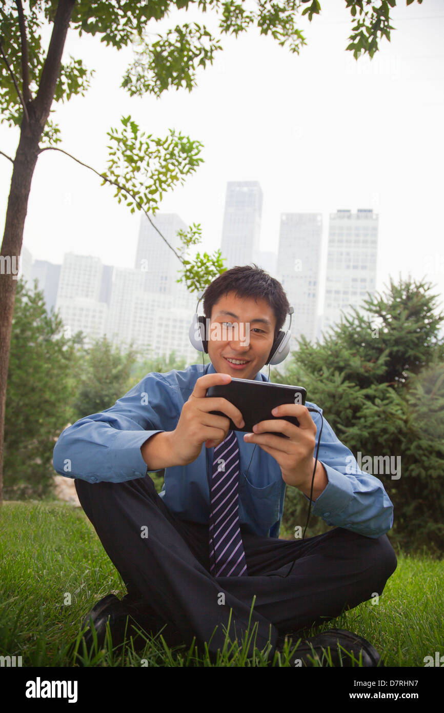 Young businessman listening to music on his MP4 player Stock Photo