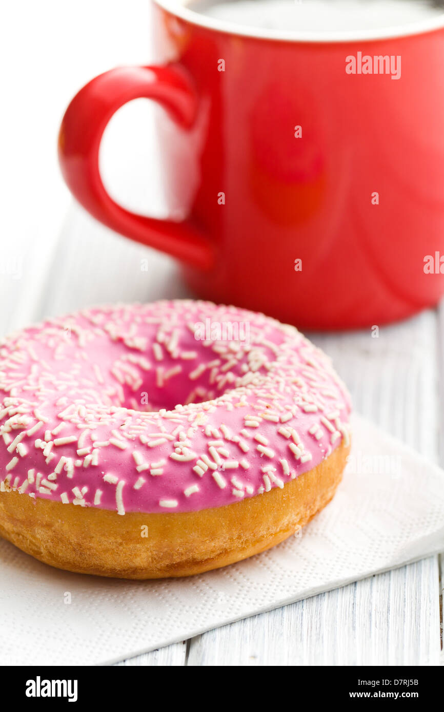 pink donut on white table - Stock Image