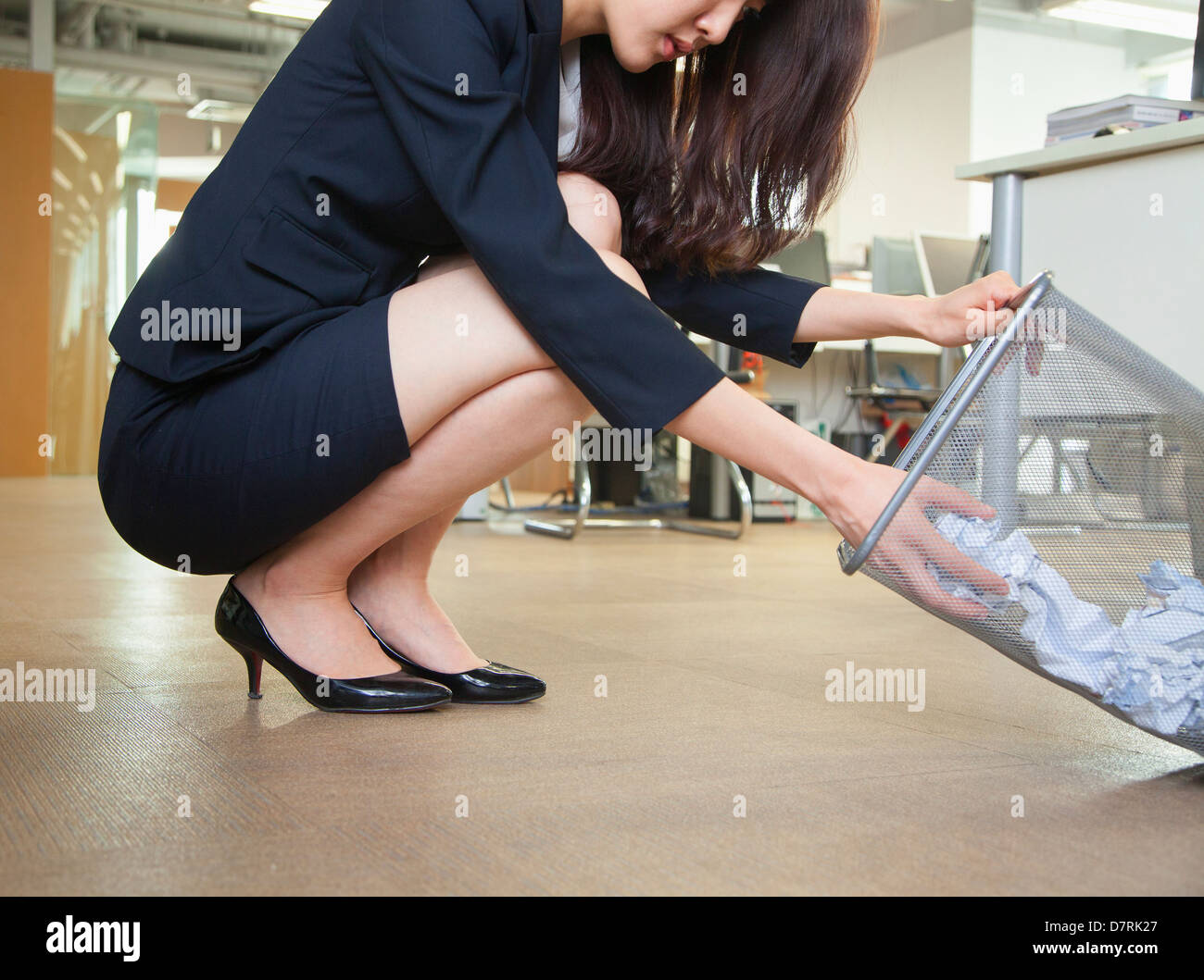Young businesswoman looking through wastepaper bin in office - Stock Image