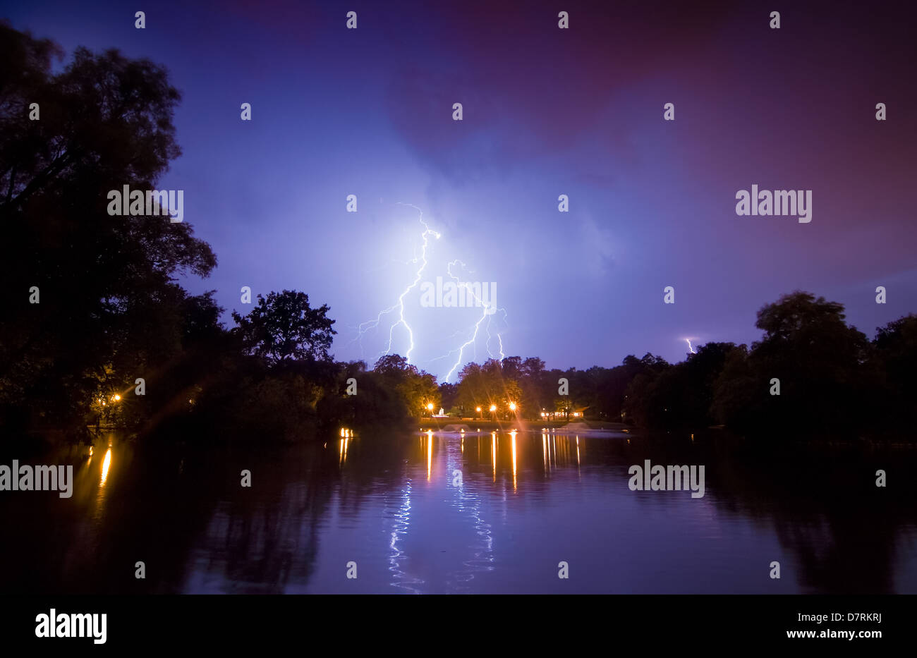 Night storm. Lightning over the pond and their reflections in the water. - Stock Image