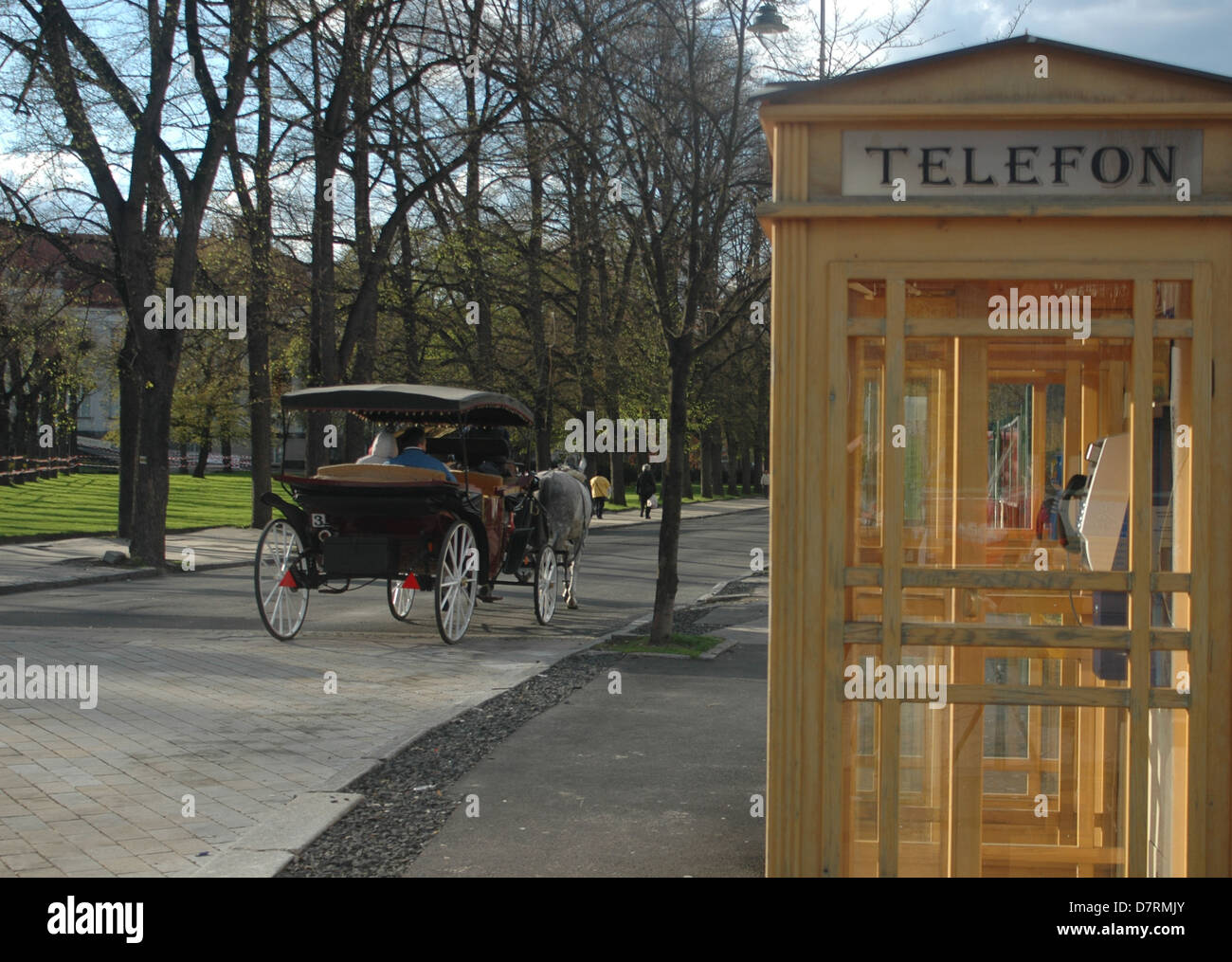 Old style telephone kiosk and a horse cart in Karlovy Vary, Czech Republic, Europe - Stock Image