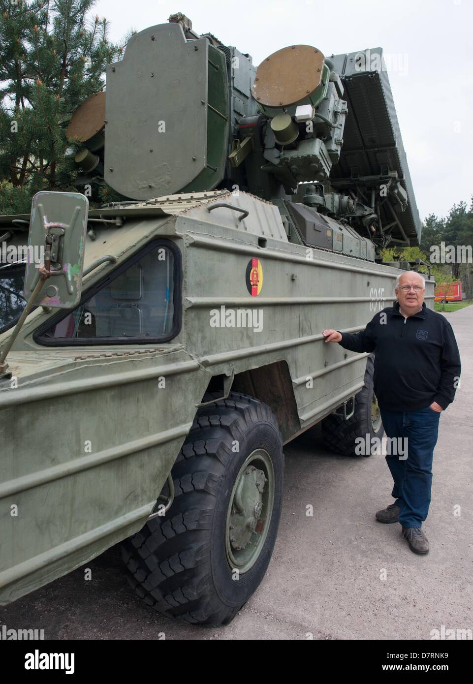 Director of the Aviation Museum Finowfurt e.V., Klaus-Peter Kobbe, stands next to a type Osa-AK air defence missile - Stock Image