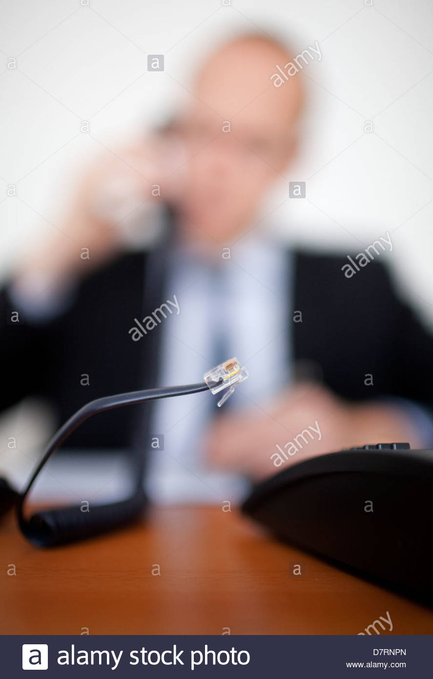 Unplugged cable of a telephone with a businessman in the background - Stock Image