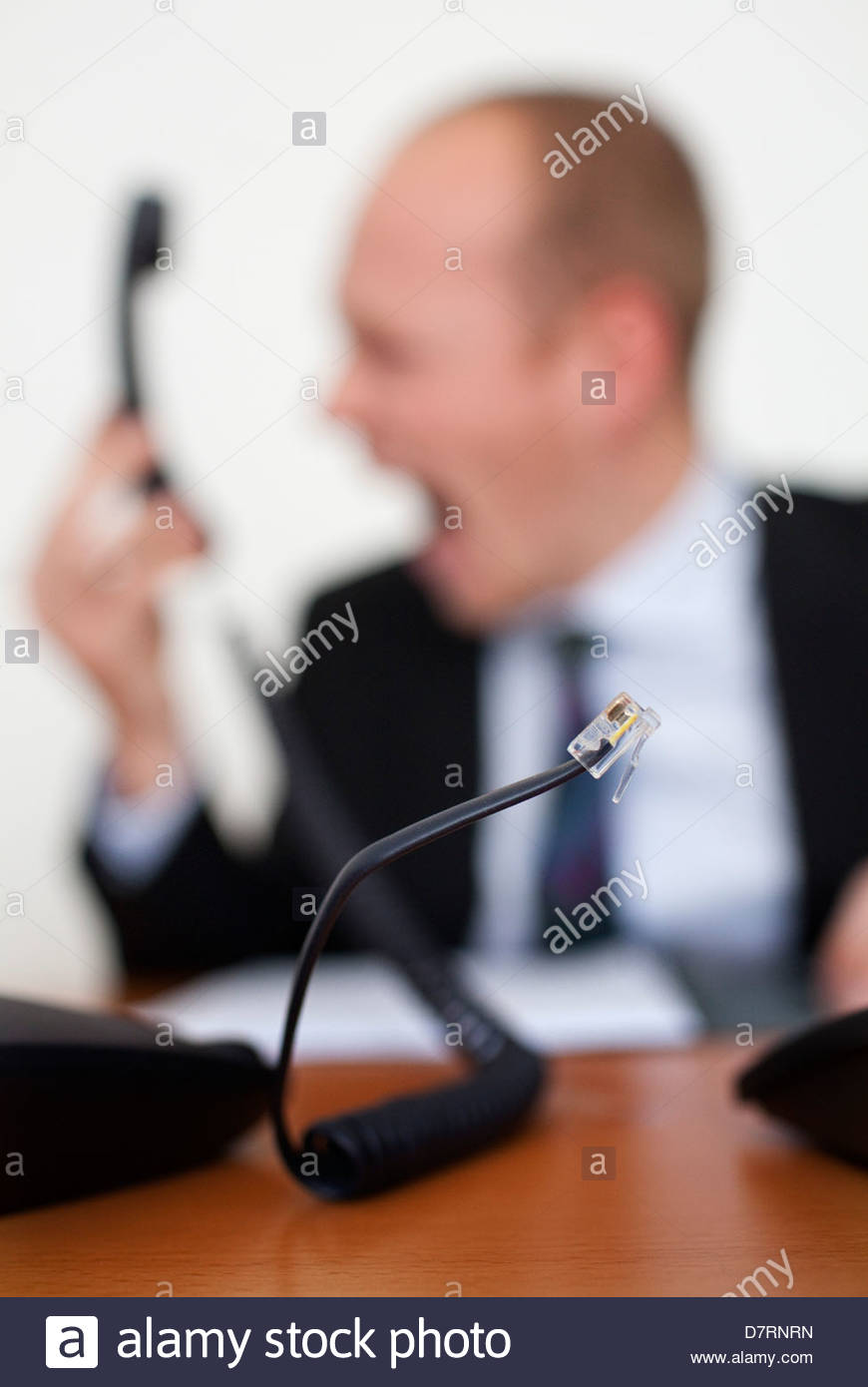 Unplugged cable of a telephone with a businessman shouting in the background - Stock Image