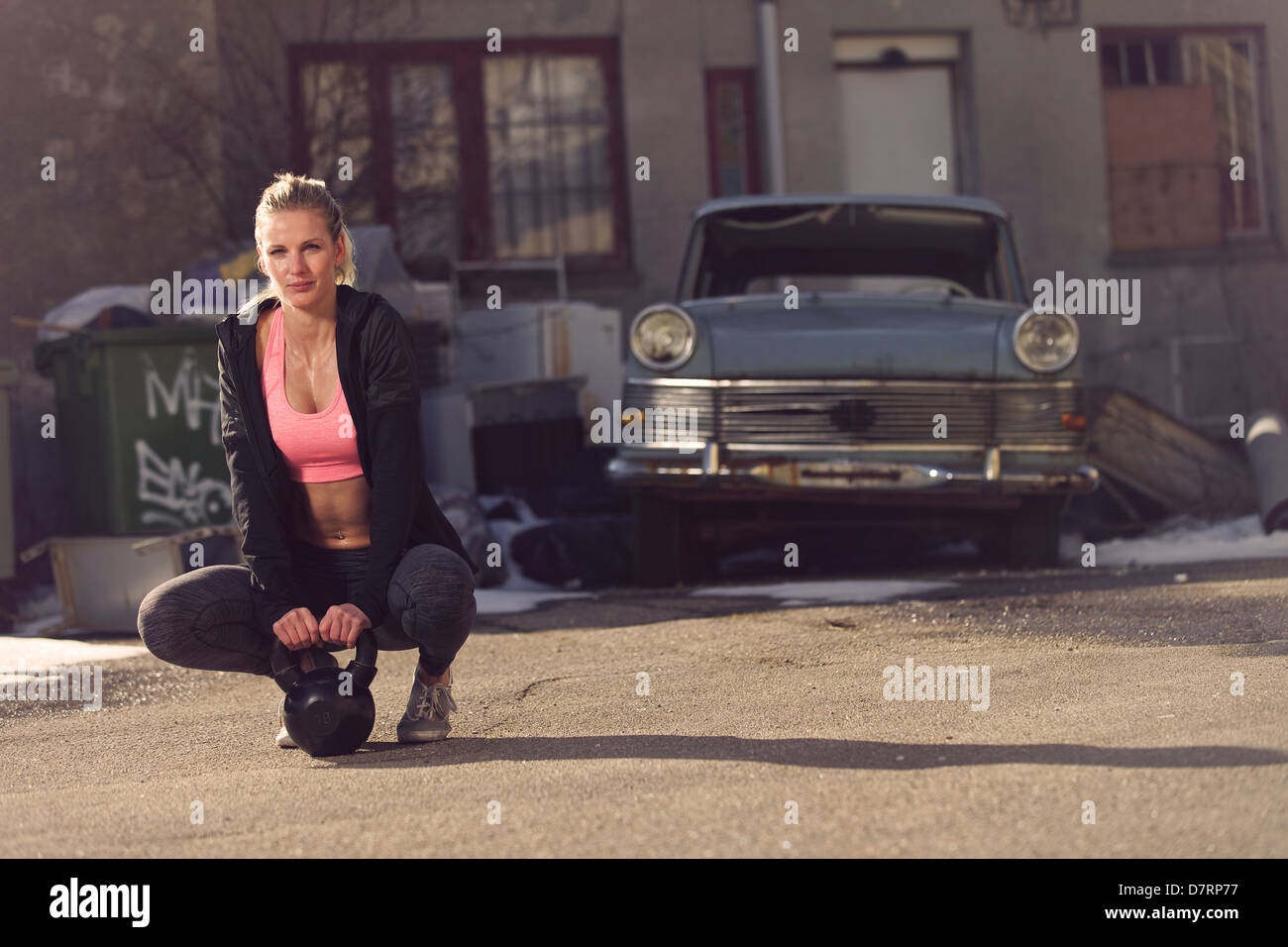 Resting fitness woman on the street having a break after exercising - Stock Image