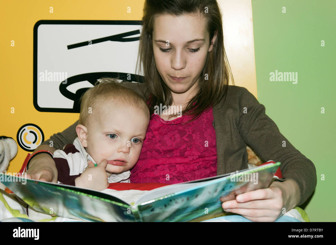 Young girl reading a story to a little boy. - Stock Image