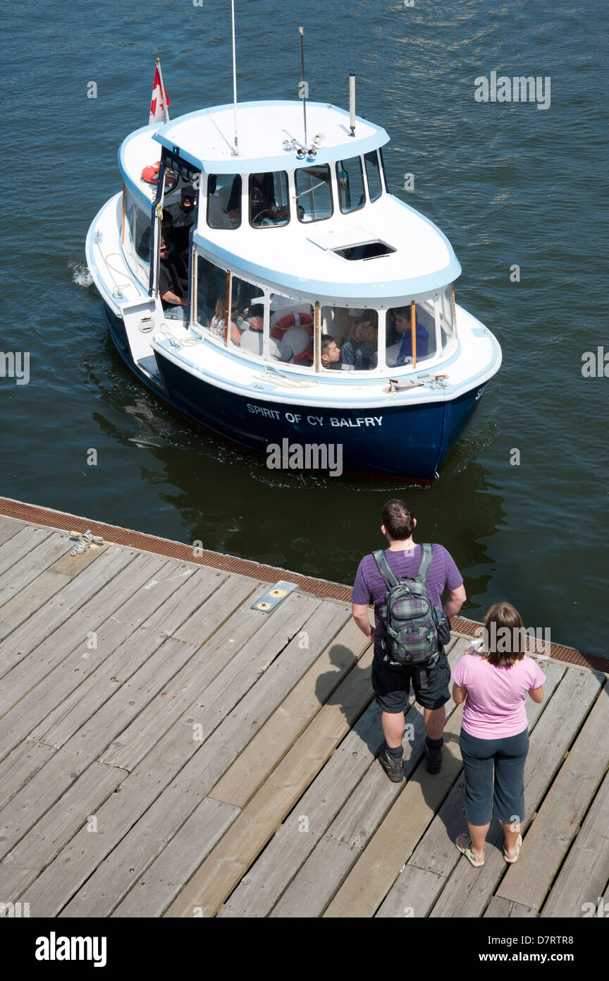 Passengers wait at the dock at Granville Island as the Granville Island ferry approaches, Vancouver, British Columbia, - Stock Image