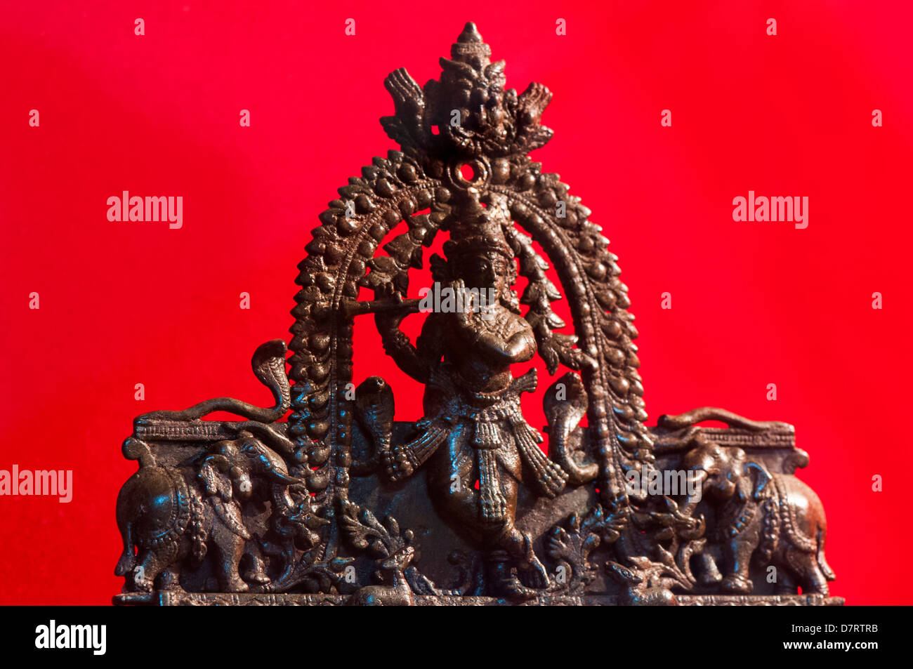 Lord Krishna playing flute stone statue - Stock Image