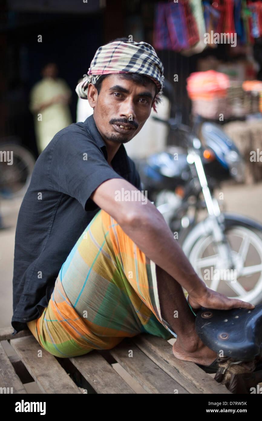 A cart puller at rest near the Chowk Bazaar, Dhaka, Bangladesh - Stock Image