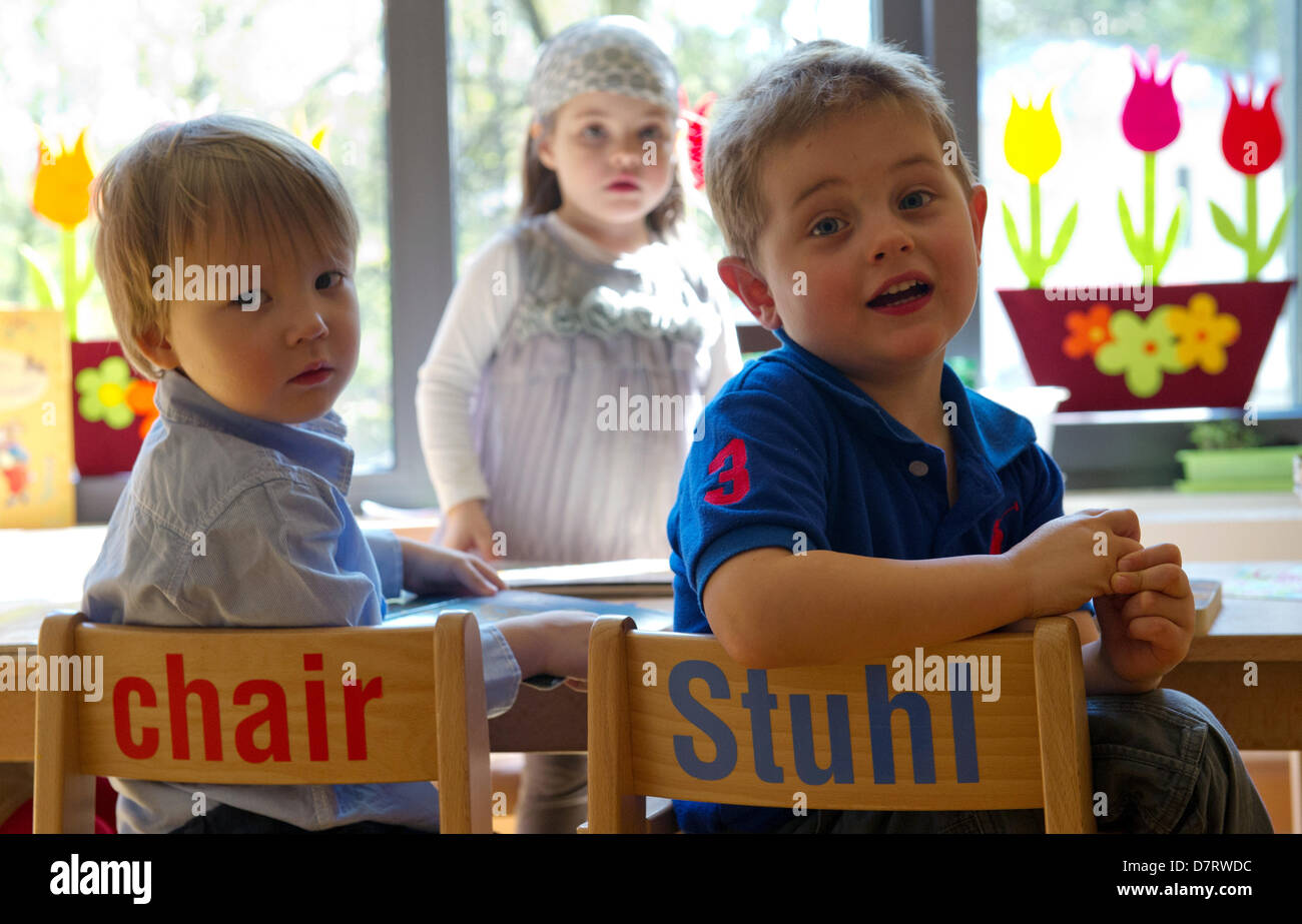 Michael Zawrel (L-R), Alba Aders und Benjamin Hewry sit on chairs with the lettering 'chair - Stuhl' at daycare Stock Photo