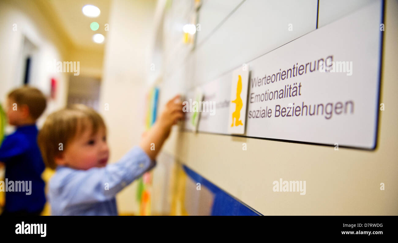 Michael Zawrel takes a magnet from the magnetic board with the lesson plan at daycare centre 'Wichtel Akademie' Stock Photo