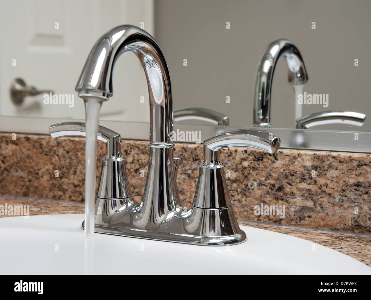 Bathroom taps with water running into sink - Stock Image