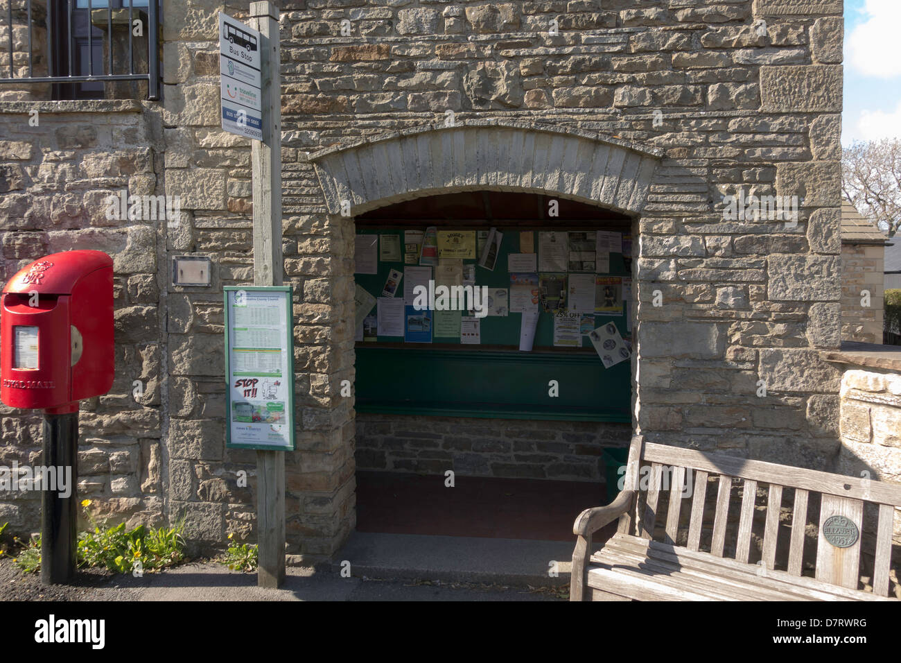 Substantial stone built village bus shelter with local notices inside in Aysgarth North Yorkshire - Stock Image
