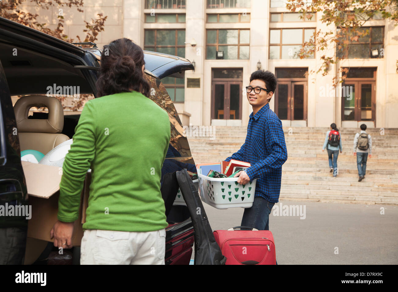 Young man moving into dormitory on college campus - Stock Image