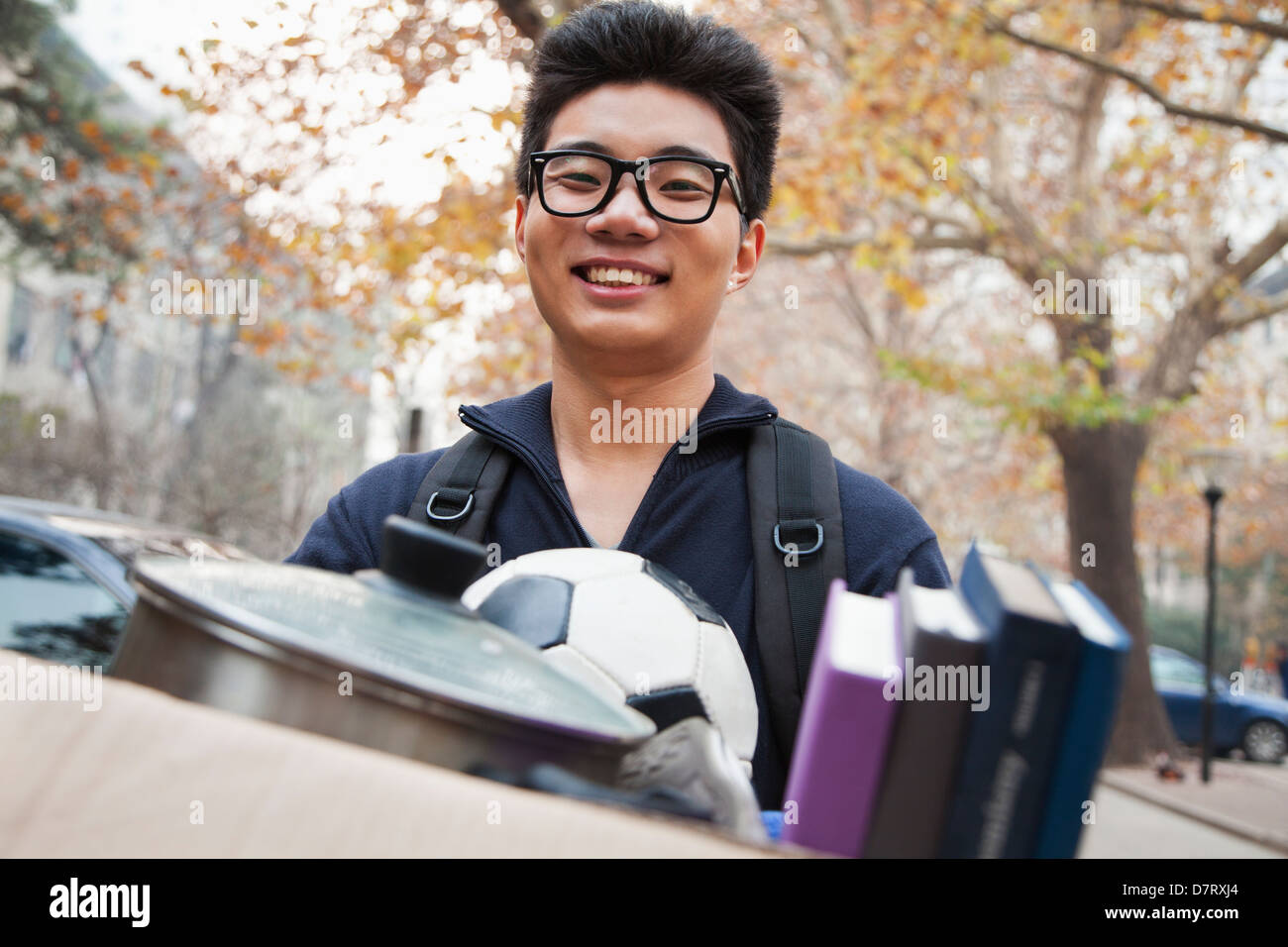 Student in front of dormitory at college - Stock Image