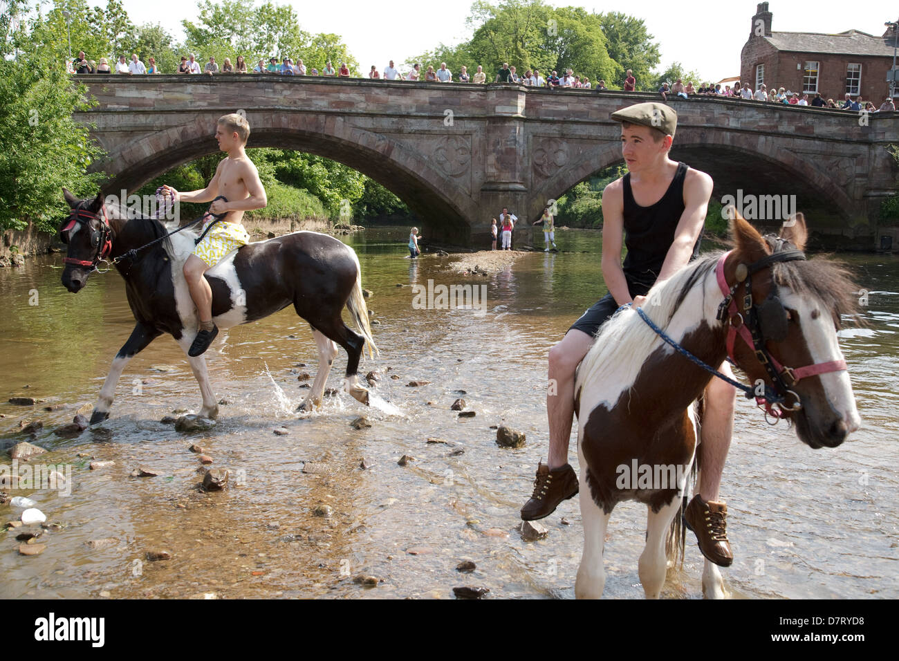Boys riding horses in the river Eden during the Appleby Fair, an annual gathering of Gypsy and Traveller communities Stock Photo