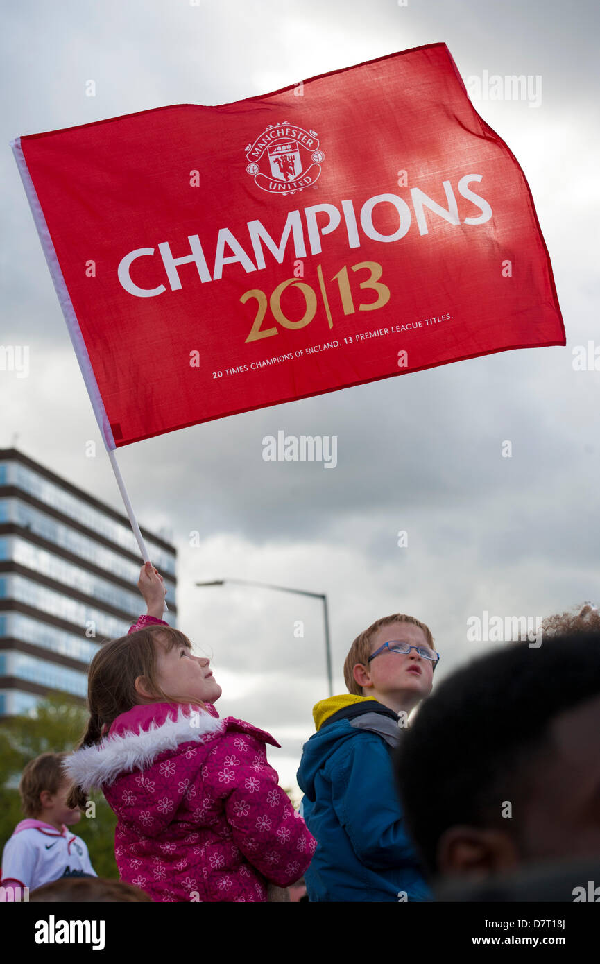 Manchester, UK. 13th May, 2013. girl holds aloft a manchester united champions flag at the victory parade for the - Stock Image