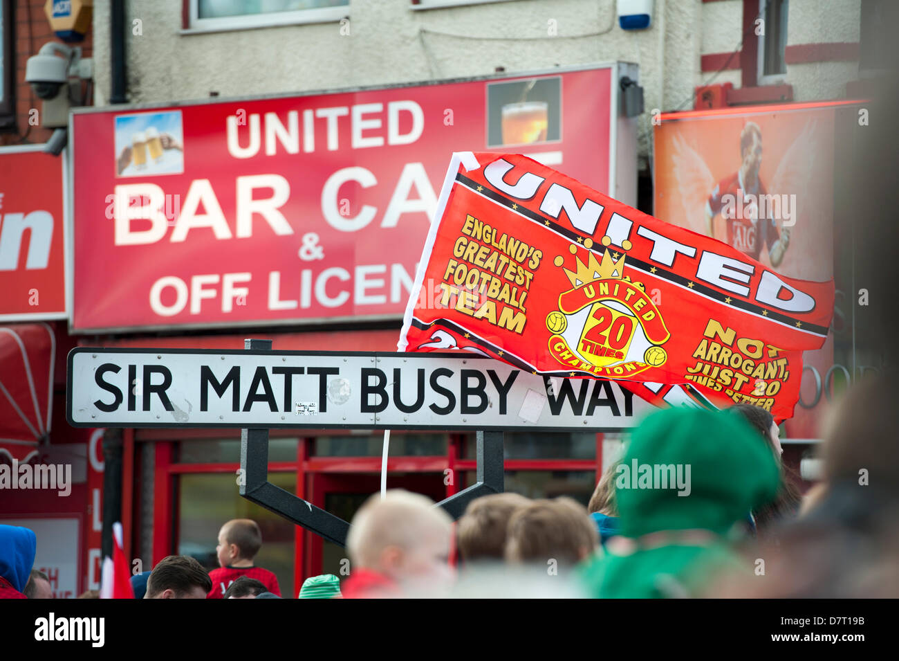 Manchester, UK. 13th May, 2013. flags draped over the road sign for Sir Matt Busby Way outside old trafford football - Stock Image
