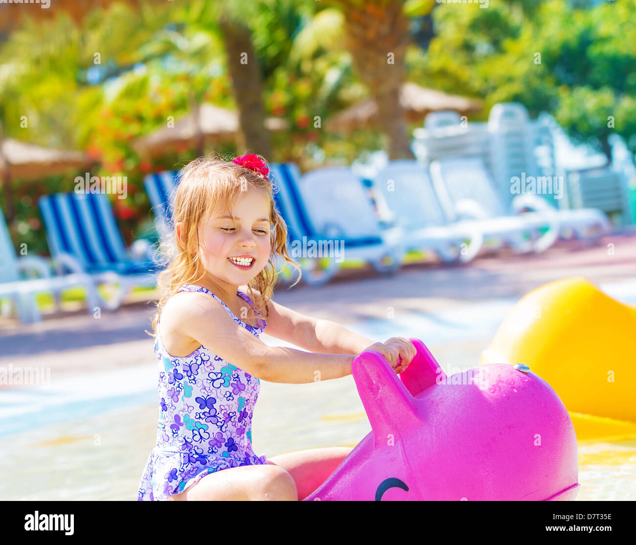 Happy baby girl having fun in aquapark, swimming in the pool on pink inflatable toy, daycare in summertime - Stock Image