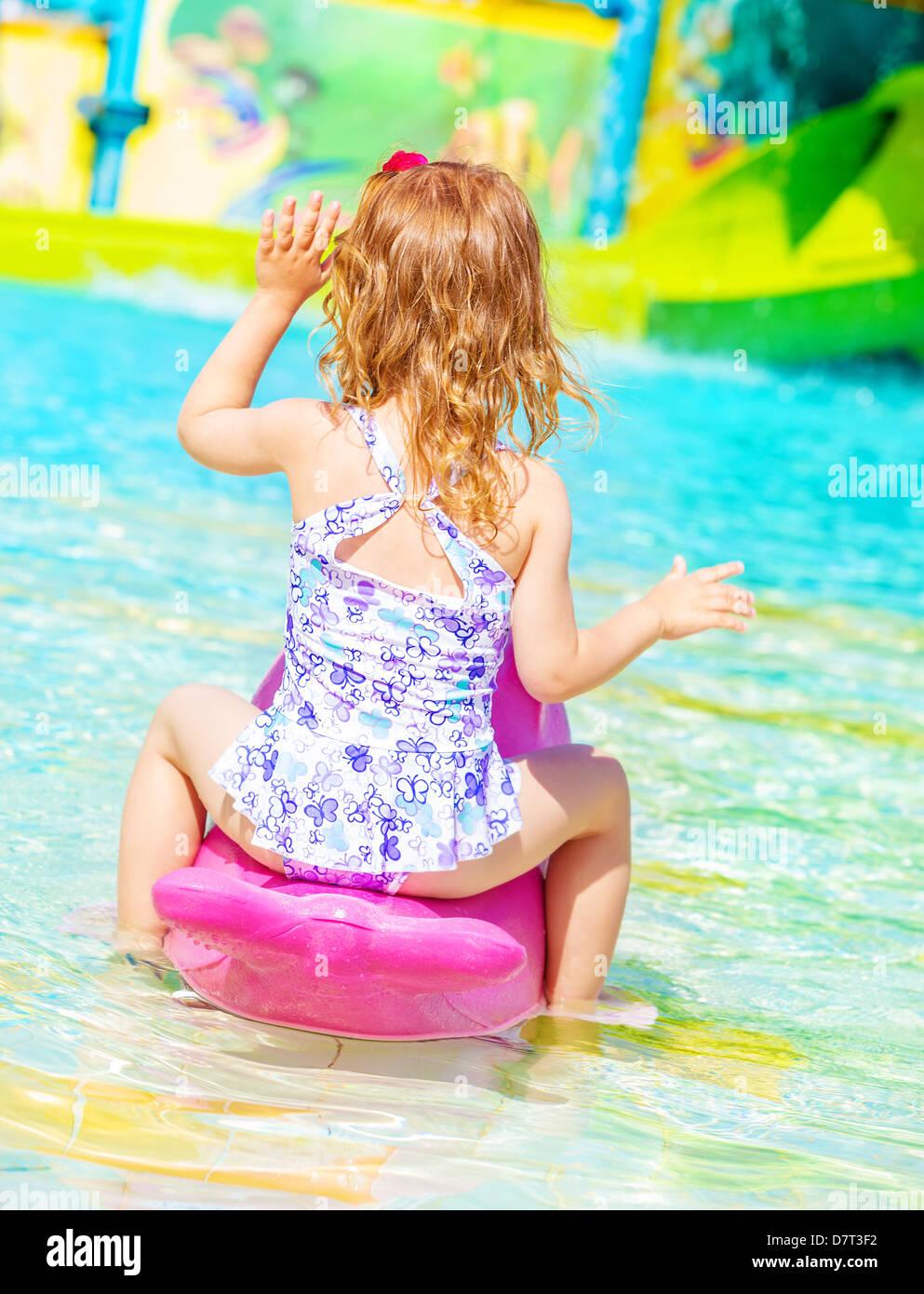 Little girl in bikini rear view Rear view of sweet little girl wearing beautiful swimwear having fun on  water attractions in aquapark, happy childhood, summer