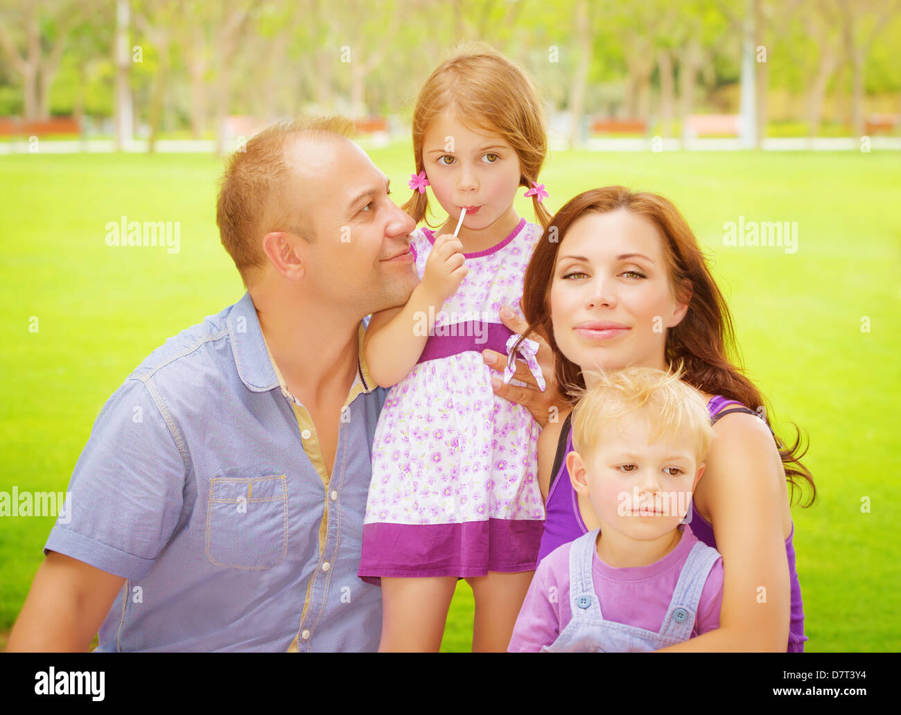 Portrait of happy family having fun outdoors, young parents with two cute kids in spring park, spending time together - Stock Image