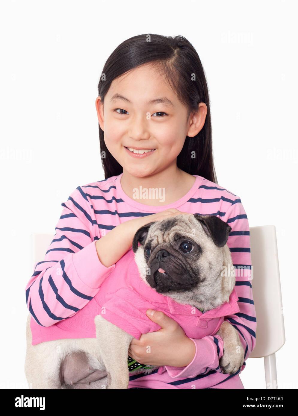Portrait of girl holding pet pug - Stock Image
