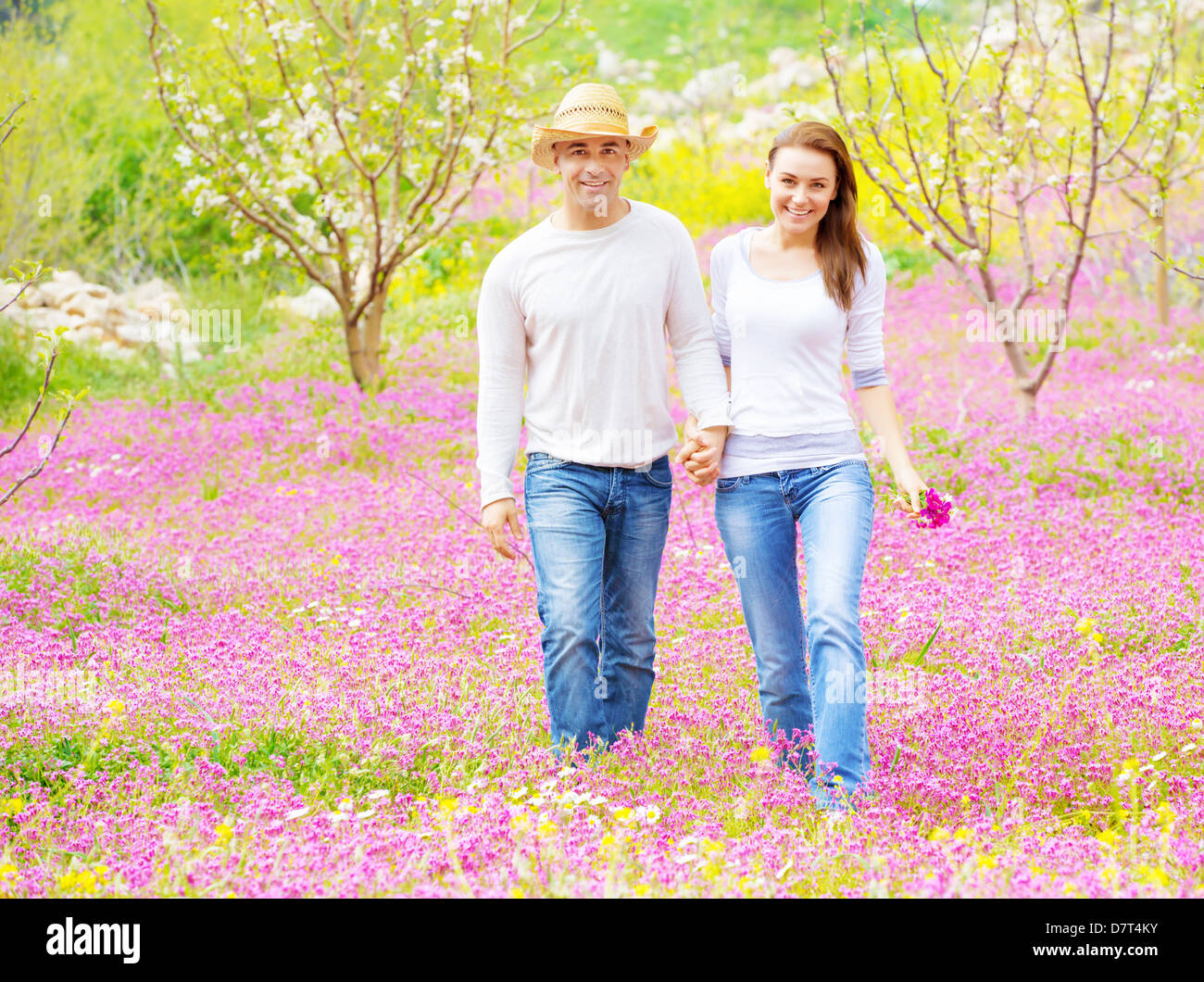 Two cheerful lovers walking in spring garden, having fun outdoors, relaxation on backyard, romance and love concept - Stock Image