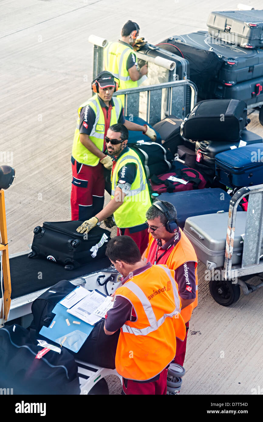 Swissport baggage handlers loading luggage into hold using conveyor belt to aircraft Lanzarote Spain - Stock Image