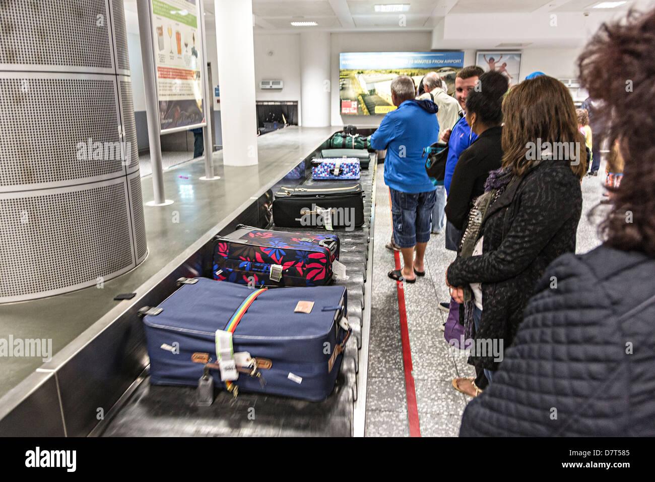 Passengers waiting to reclaim luggage at Bristol airport, UK - Stock Image
