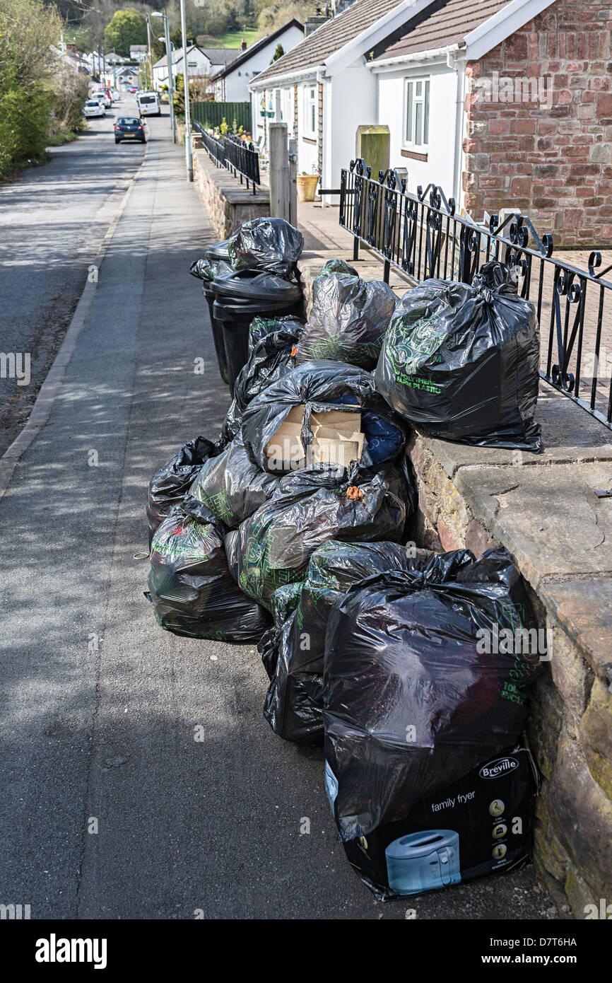 Black bag kerbside collection waste in village street, Wales, UK - Stock Image