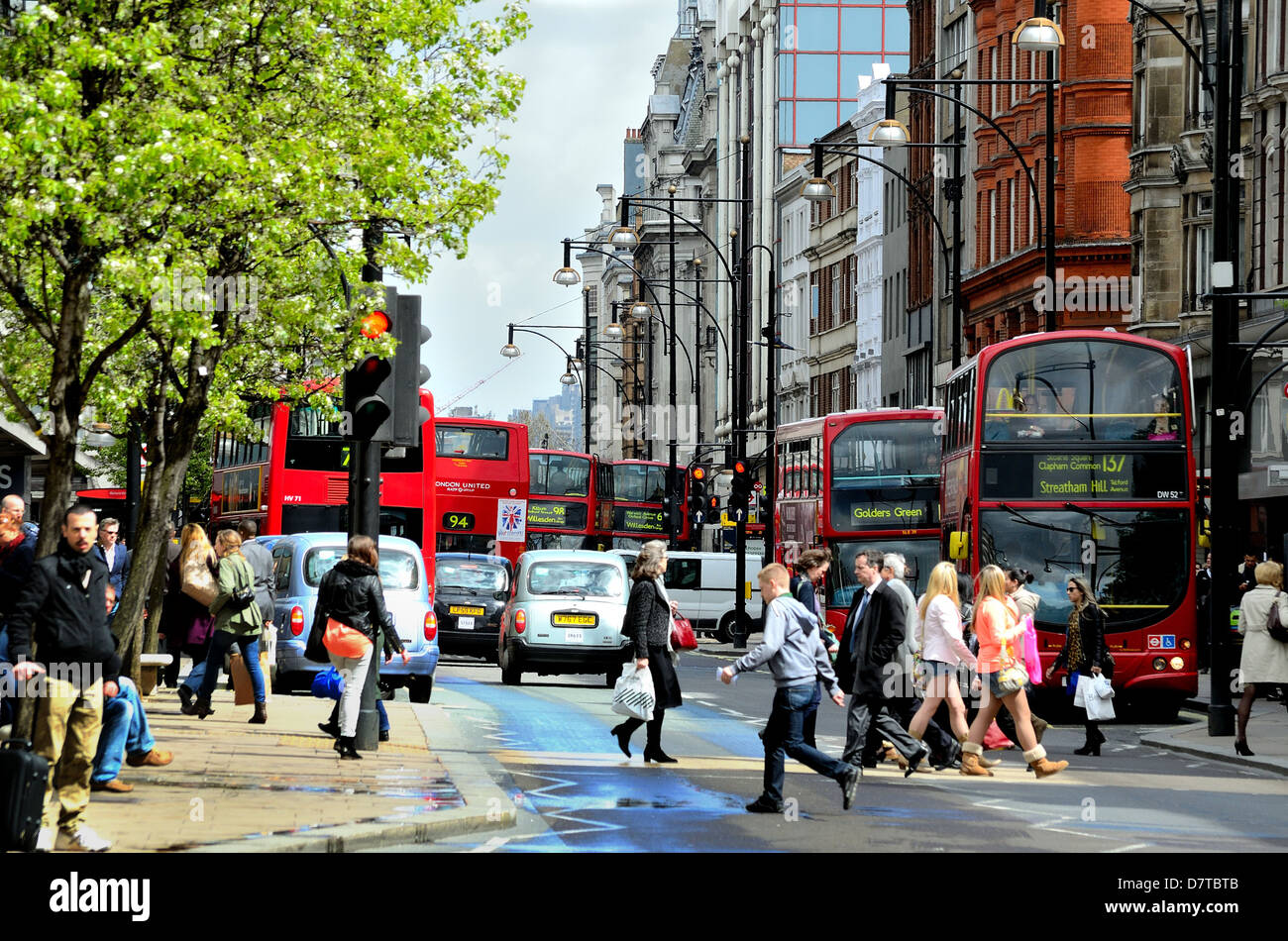 Red London buses in a busy Oxford Street UK - Stock Image