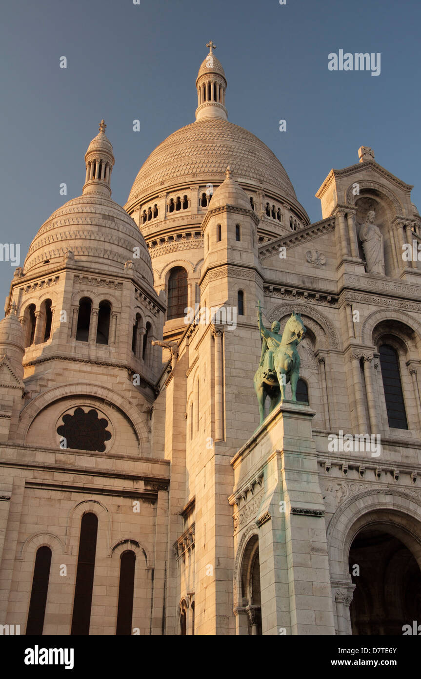 The façade and towering white domes of the basilica of Sacra-Coeur in Montmartre. Above the portico is a statue Stock Photo