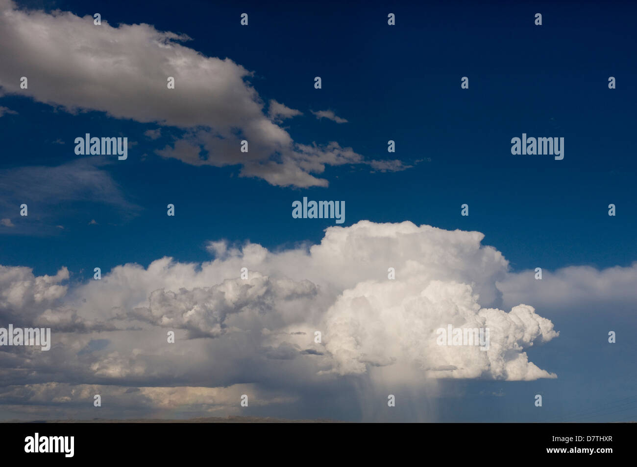 Cumulus clouds and virga (observable streak of precipitation that falls from a cloud). Interstate 80 by Rawlins, Stock Photo