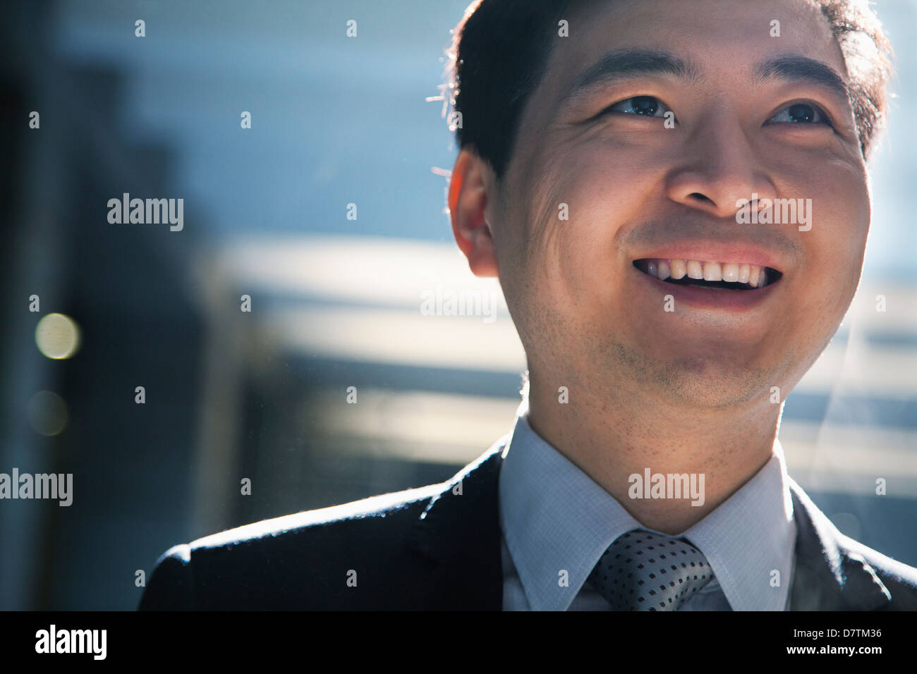 Portrait of smiling businessman in a parking garage - Stock Image