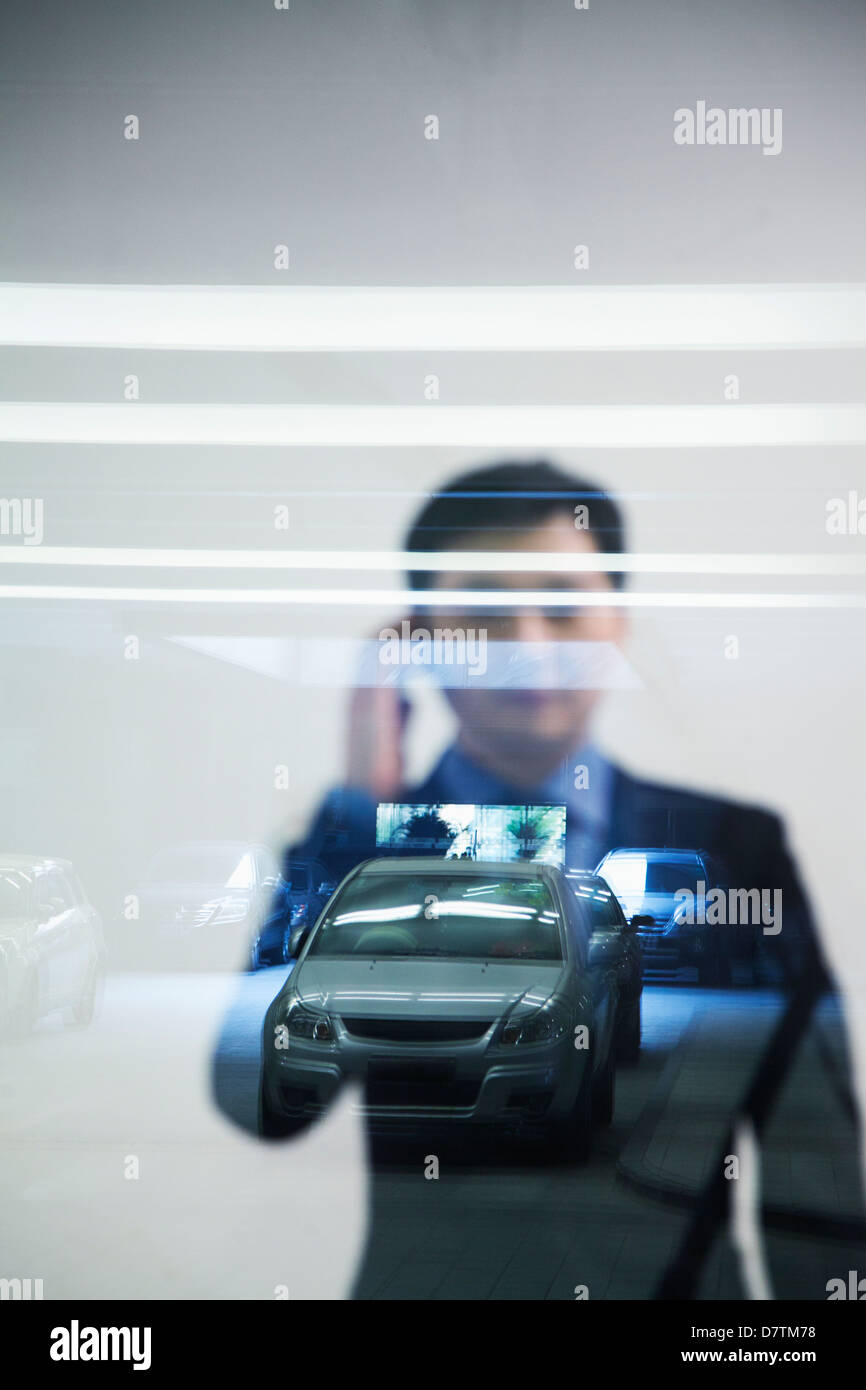 Businessman looking thorough window in parking garage, reflection of car - Stock Image
