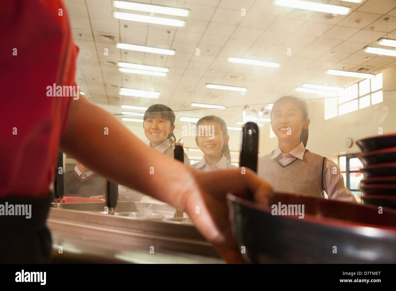 School cafeteria worker serves noodles to students - Stock Image